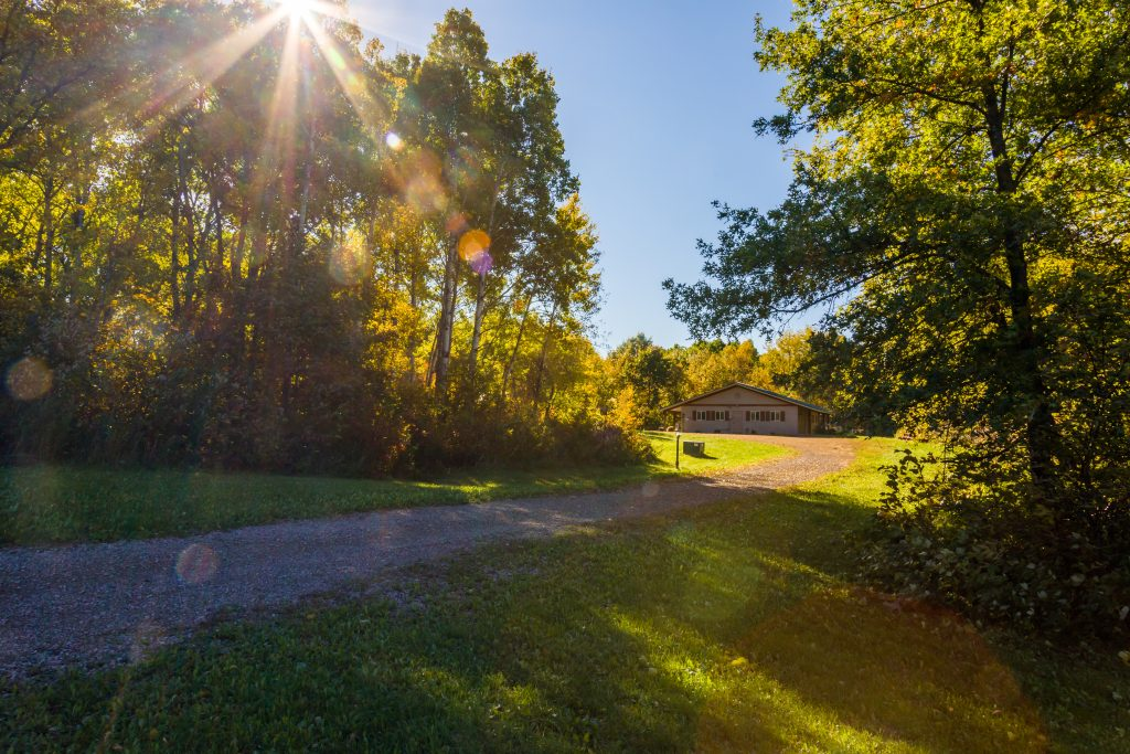 Photo of sun shining through the trees and gravel drive leading up to Diane's House at Nature's Edge Therapy Center in Rice Lake, WI.