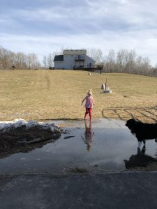 Little girl in pink jumping into large puddle at end of hill, with house on top of hill.