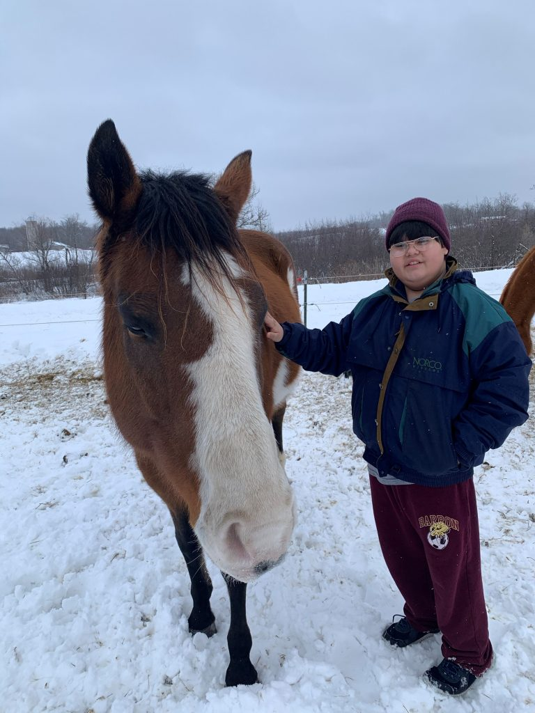 Brown and white horse with boy dressed in winter clothes standing next to horse outside in snow.